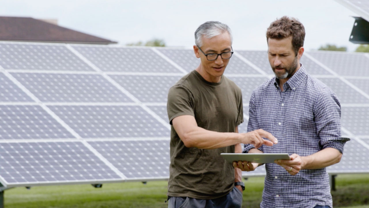 People in front of solar panels with tablet