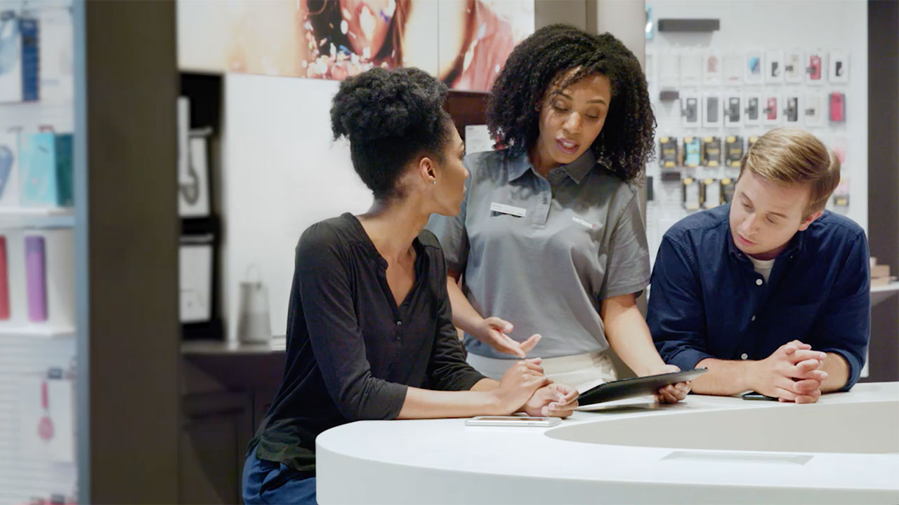 Sales person at Verizon store speaking with customers