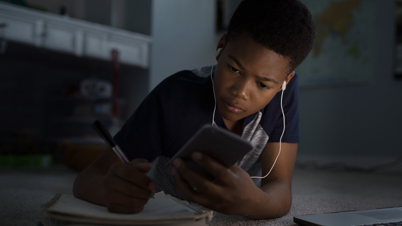 Image of a teenager on a phone.