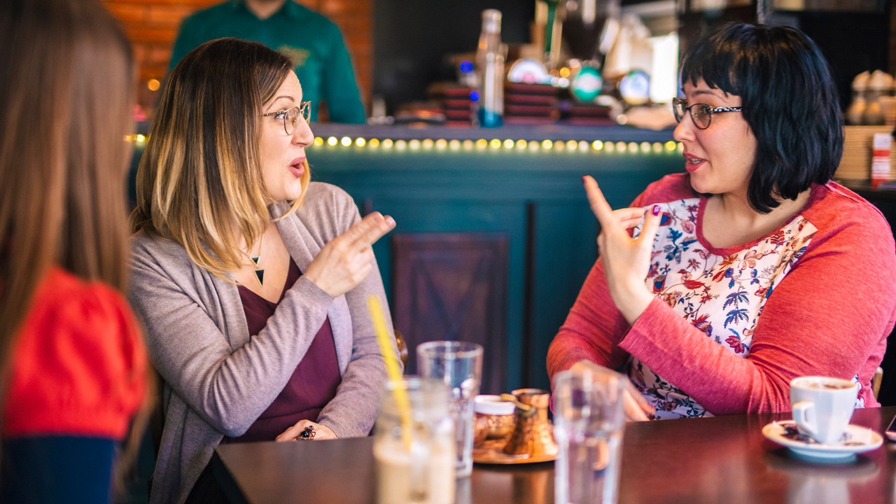 Two female friends sign to one another while sitting at a table in coffee shop while another woman looks on.