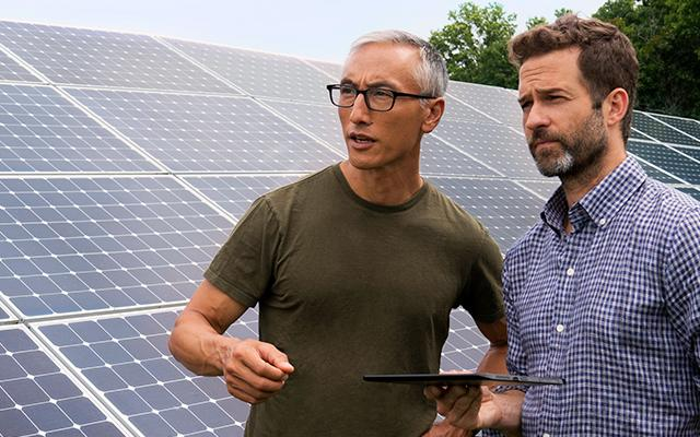 Men in front of solar panel with tablet