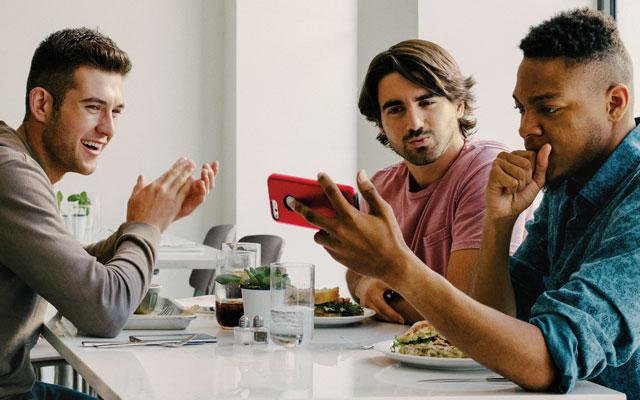 Men at cafe with mobile phone