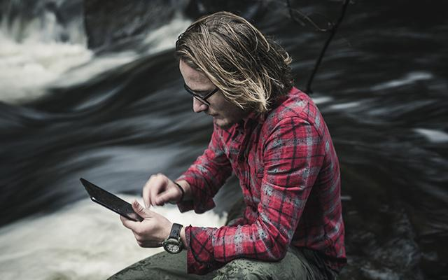 Man by river with tablet