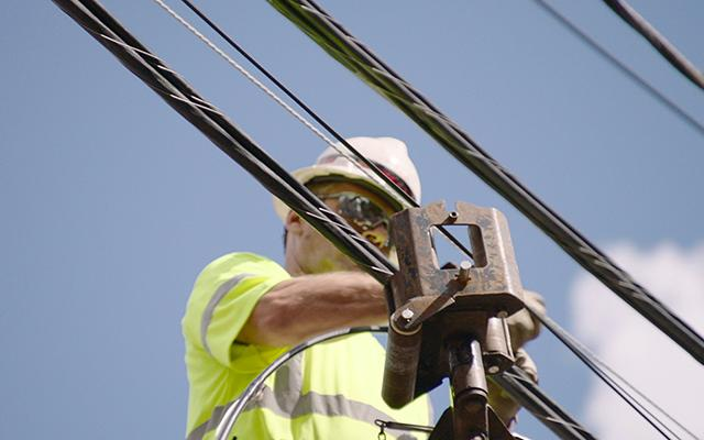 Man on pole installing fiber