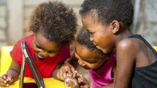 African-American children playing with tablet