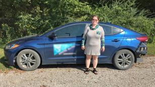 Karisa Jones in front of her car