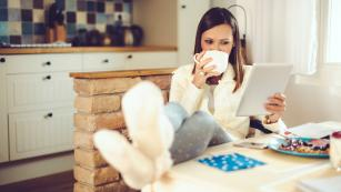 Woman sipping coffee on laptop