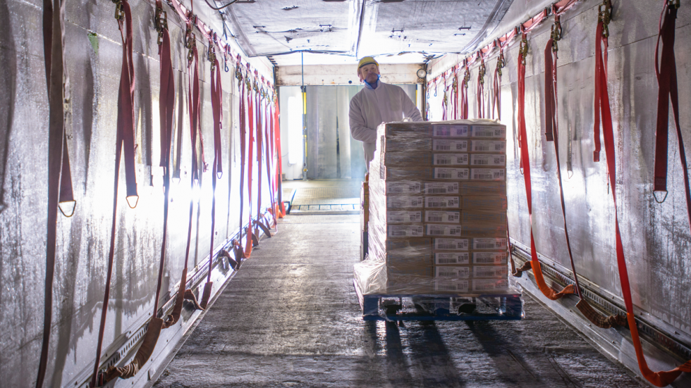 Man in warehouse pushing boxes