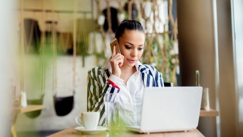 Woman in front of laptop and cell phone