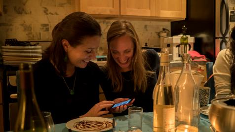 Two women looking at phone at kitchen table
