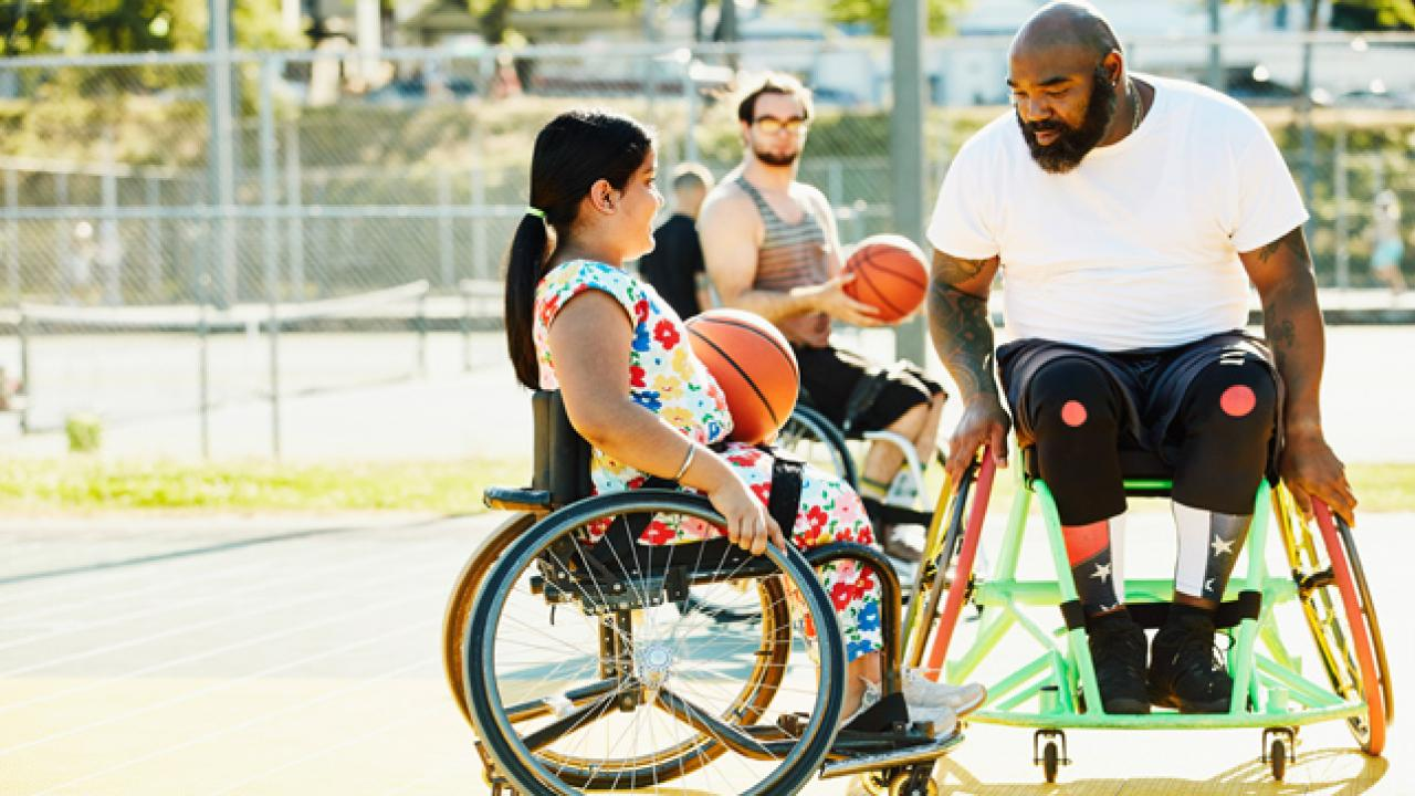 A smiling young female learning how to play wheelchair basketball from her coach, who is also in a wheelchair.