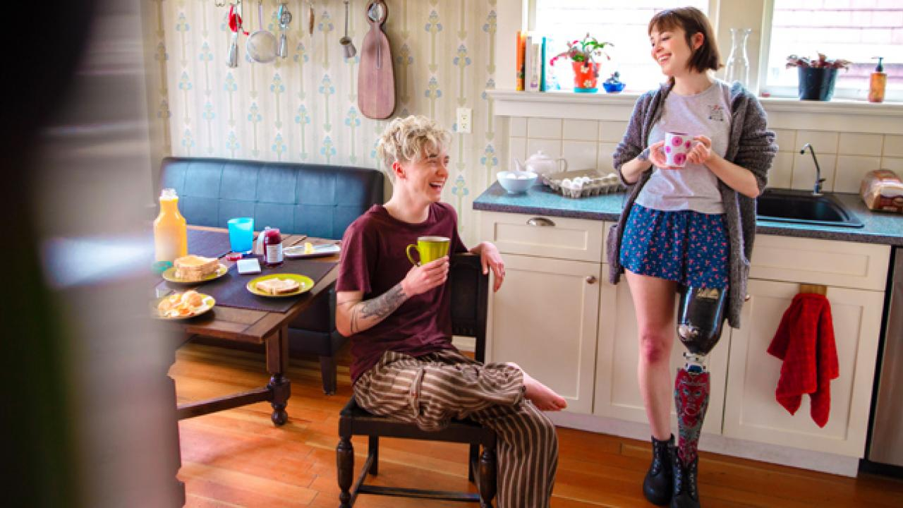 Two young women talk and drink coffee in a kitchen. The woman on the right has a prosthetic leg.