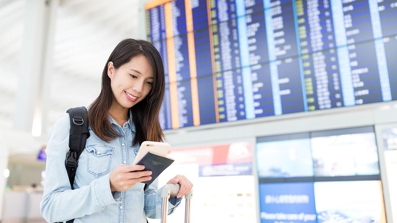 Woman on mobile phone in front of airport screen
