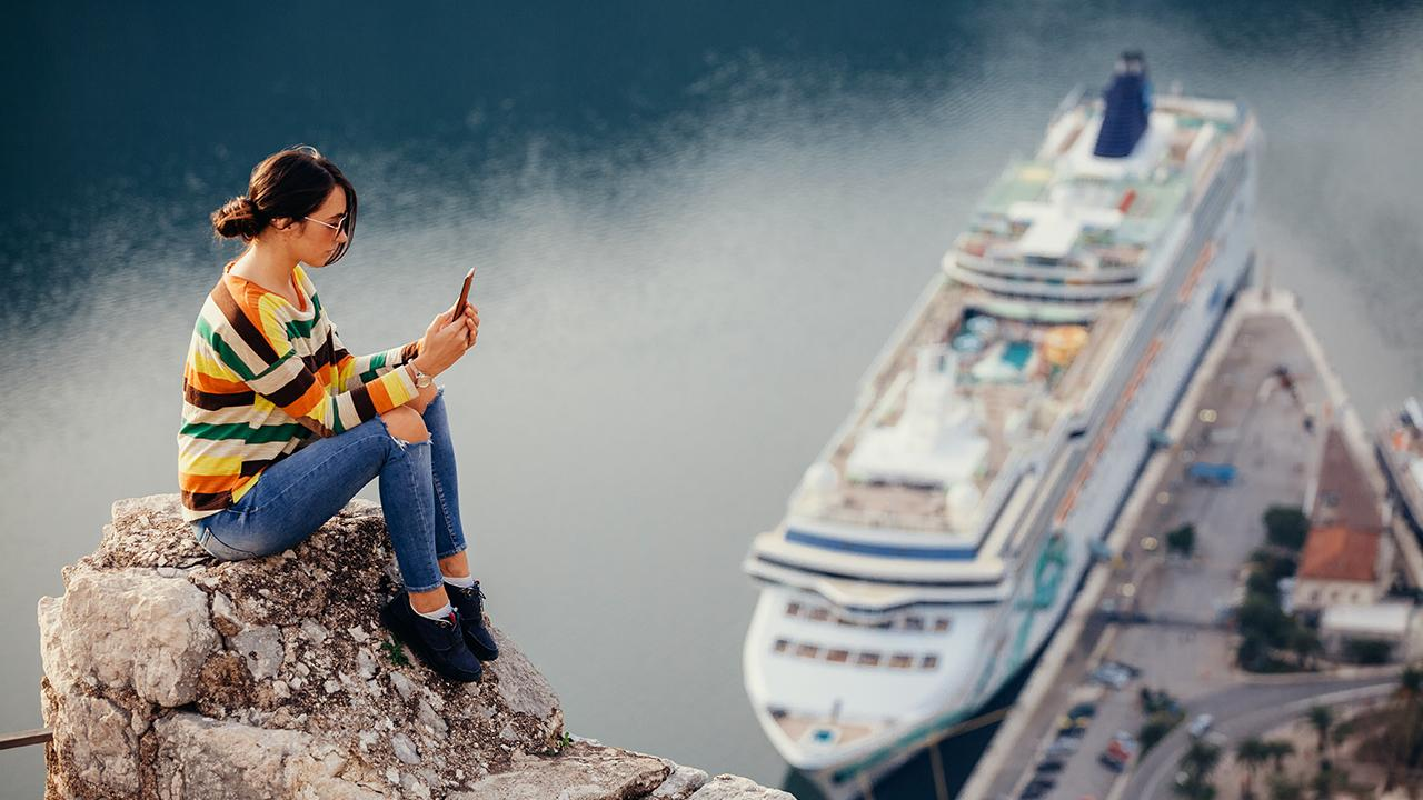 Woman on phone on top of cliff overlooking cruise ship