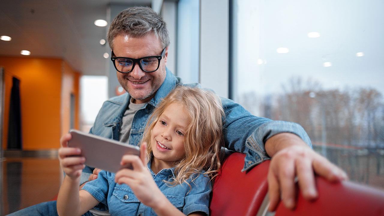 Father with child at airport holding mobile phone