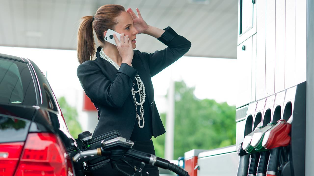 Woman at gas station with mobile phone