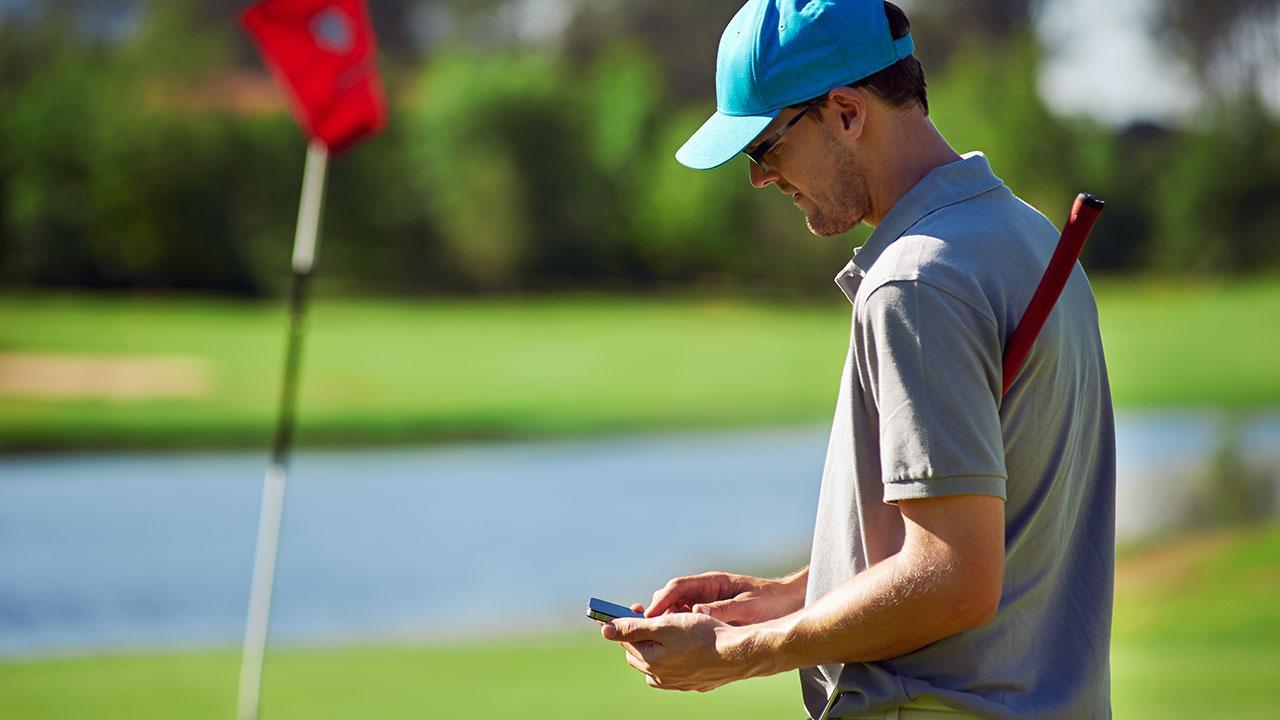 Man golfing looking at his phone