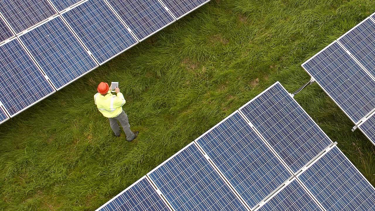 A technician works in a grass field between two solar panel arrays
