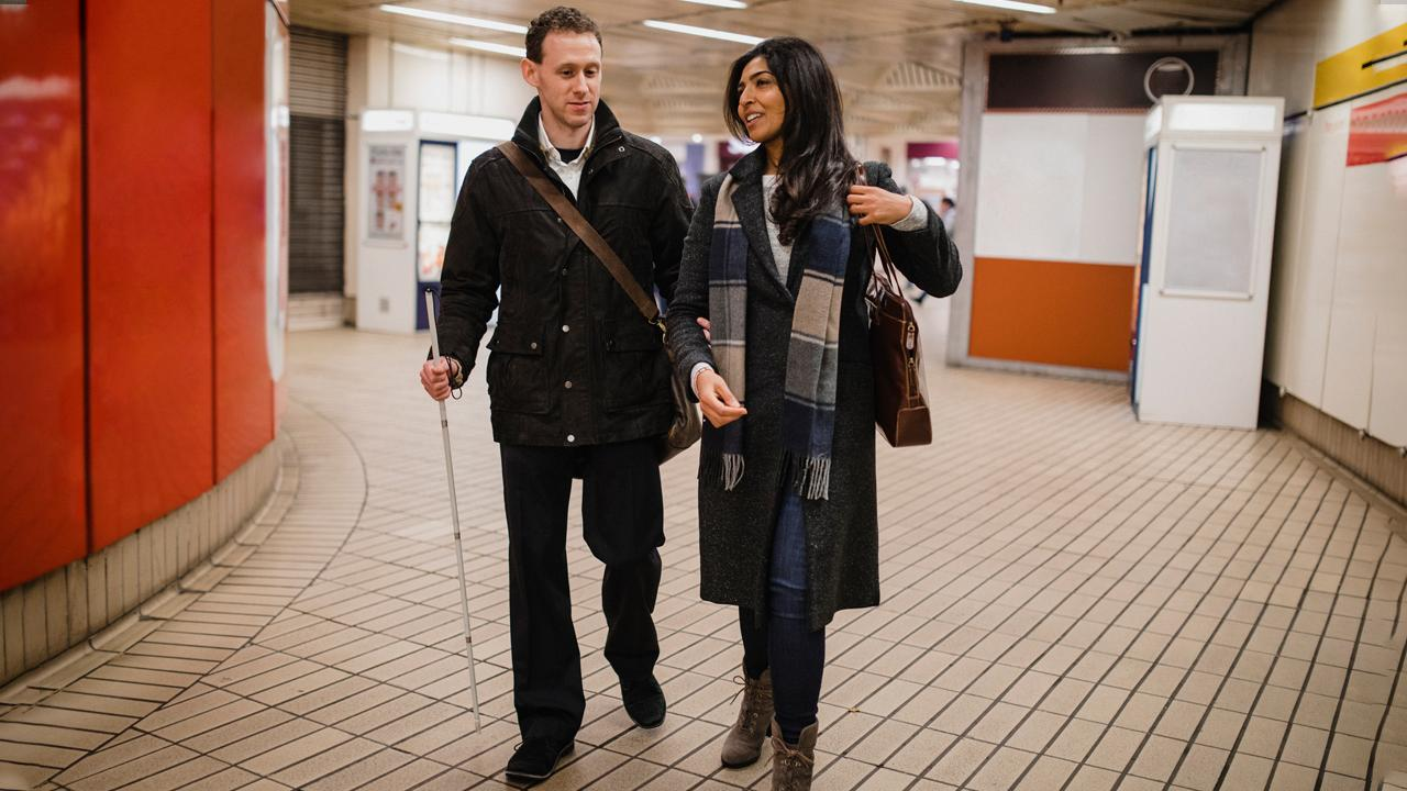 A man with a vision impairment walking with his female friend leaving a subway station, he is using a white cane and is holding his friend's arm for guidance