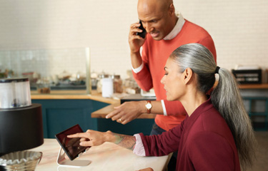 Woman and man on cellphone pointing to tablet