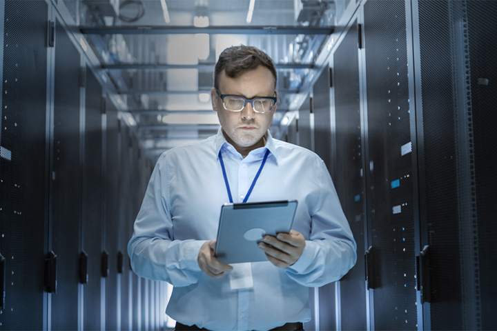IT technician walks through sever room in data center while using a tablet