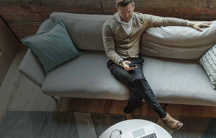Man sitting on couch using mobile device