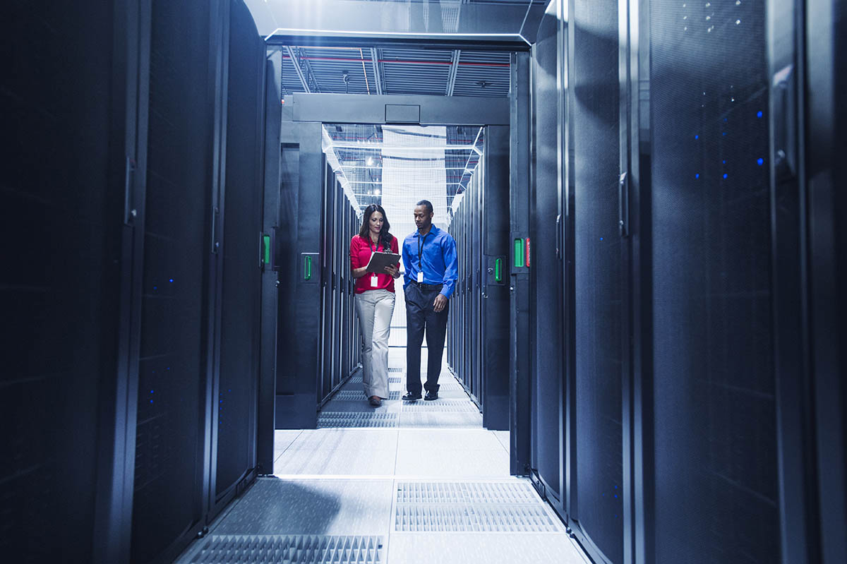Man and woman walking through a room of larger data servers