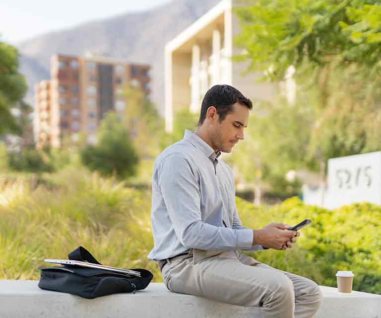 Man sitting outside looking at his smartphone