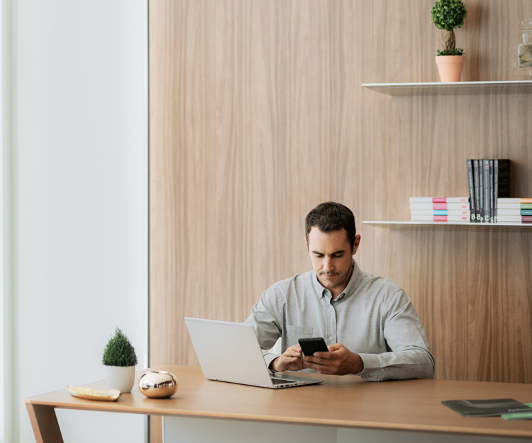 Man using smartphone while sitting at desk