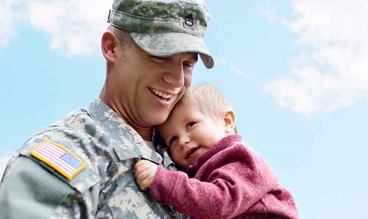 A military service member smiles while holding his child.