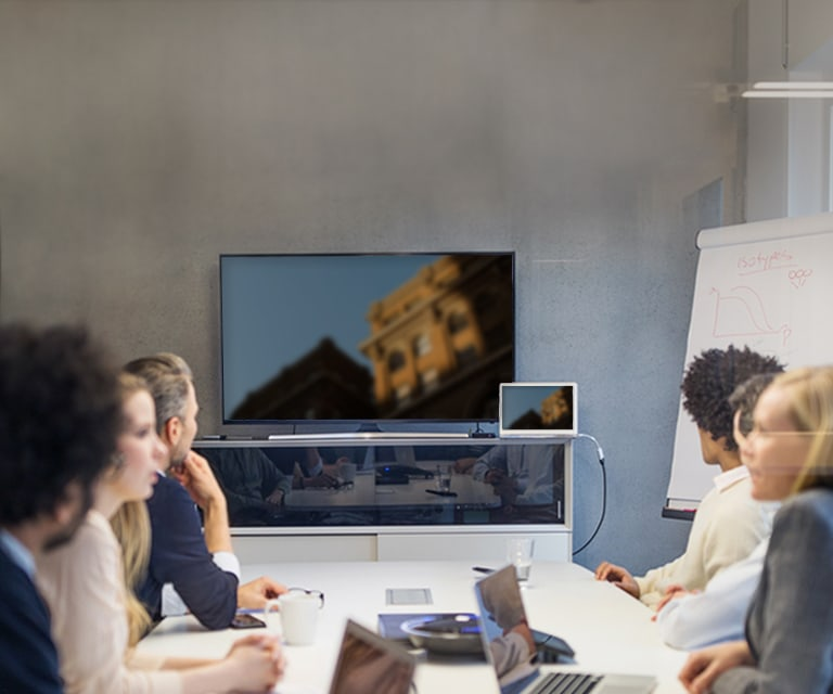 A group of coworkers at a conference table with a TV in the background.