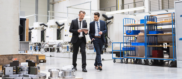 Two men in suits walking through a warehouse