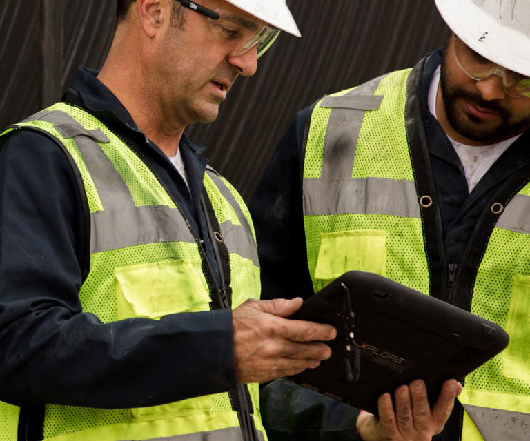 Men in hard hats looking at a tablet