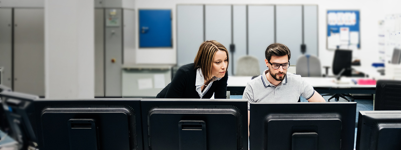 Two coworkers collaborate at a desk in front of a row of computer monitors
