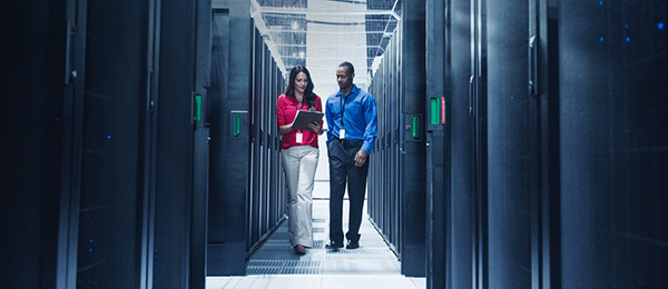 Two workers walk through a server room.