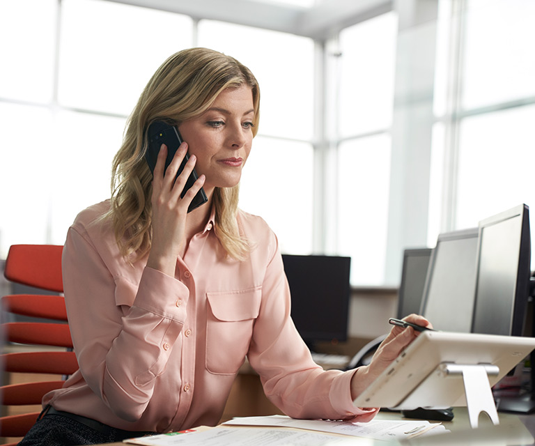 A woman in an office speaks on the phone while using a tablet.
