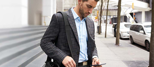 Man in suit looking at his phone.