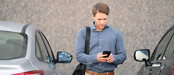 A man uses his smartphone in a parking lot.