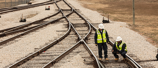 Two workers examine a railroad.