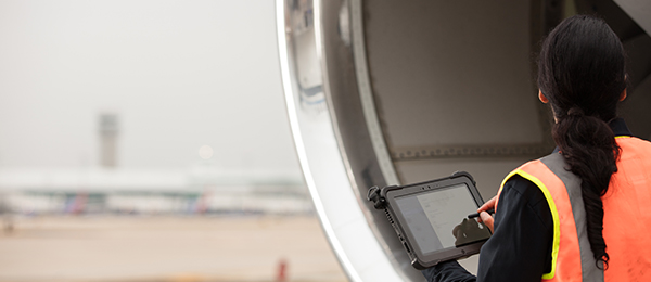 A woman uses a tablet while standing next to a jet engine.