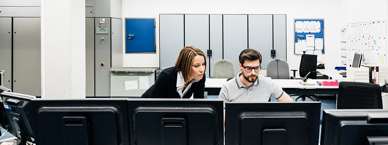 man  and woman looking at monitor