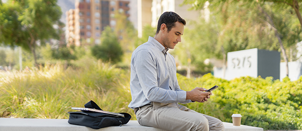 Man sitting outside looking at his smartphone.