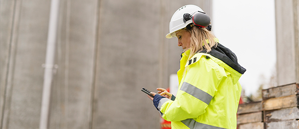 Woman in construction gear looking at her phone.