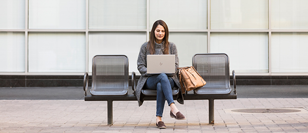A woman works outdoors on her laptop