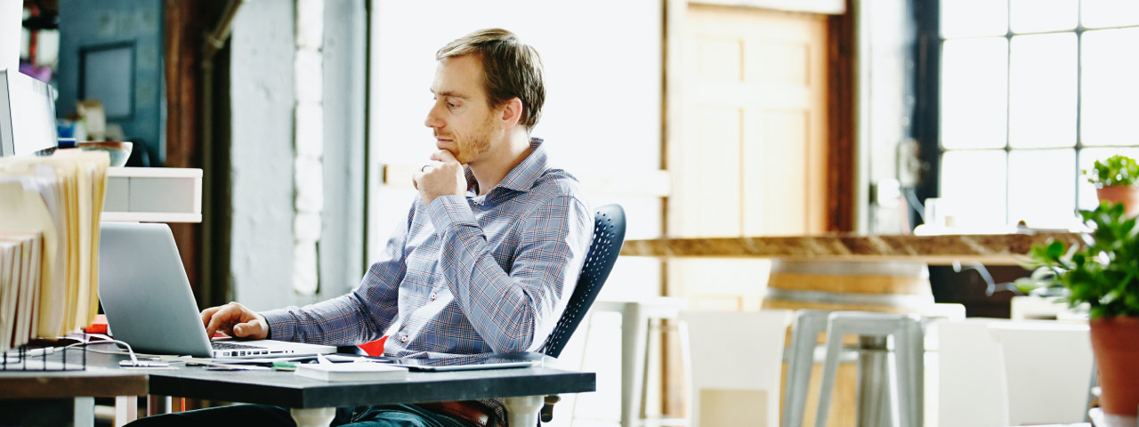 man sitting at table looking at laptop