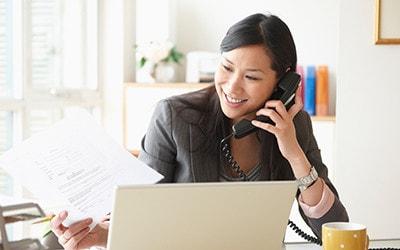 Mujer empresaria en el escritorio de la oficina usando el servicio Fios Voz digital.