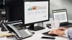 PC portátil, monitor y teléfono sobre el escritorio de una oficina.