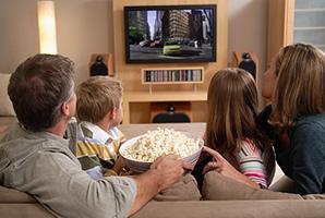Familia en un sofá comiendo palomitas de maíz mientras disfruta de Fios TV por cable.