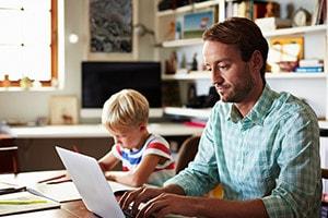 Padre e hijo trabajando sobre una mesa.