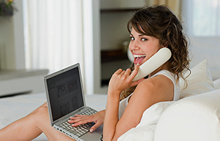 Mujer usando Fios Voz digital mientras usa su laptop.